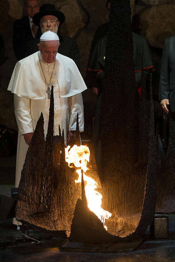 In this photo provided by the Vatican newspaper L'Osservatore Romano, Pope Francis rekindles the Eternal flame at the Hall of Remembrance at the Yad Vashem Holocaust memorial in Jerusalem, Monday, May 26, 2014. (AP Photo/L'Osservatore Romano, ho)