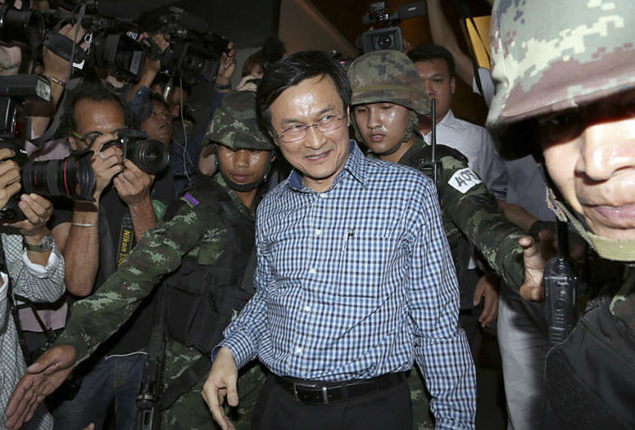 Former Thai Education Minister Chaturon Chaisang, center, walks after being detained by soldiers after a news conference at the Foreign Correspondents' Club of Thailand in Bangkok, Thailand Tuesday, May 27, 2014. Thai troops detained the Cabinet minister who defiantly emerged from hiding on Tuesday to condemn last week's military coup and urge a return to civilian rule, in the first public appearance by any member of the ousted government. (AP Photo/Apichart Weerawong)