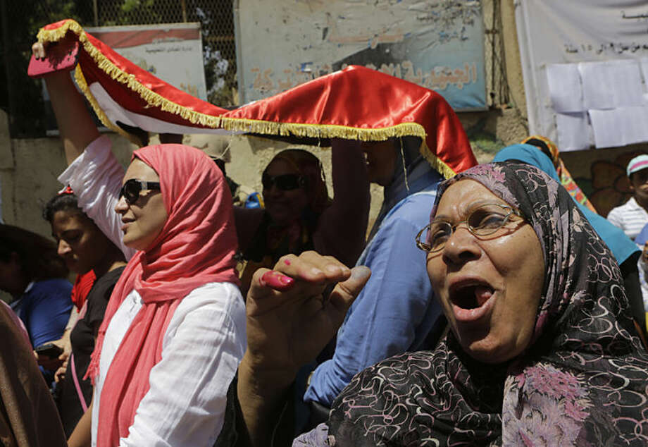 An Egyptian voter ululates after she casts her vote outside a polling station during the first day of presidential elections in Cairo, Egypt, Monday, May 26, 2014. The man who removed Morsi, retired military chief Field Marshal Abdel-Fattah el-Sissi, is practically assured of a victory in the vote. (AP Photo/Amr Nabil)