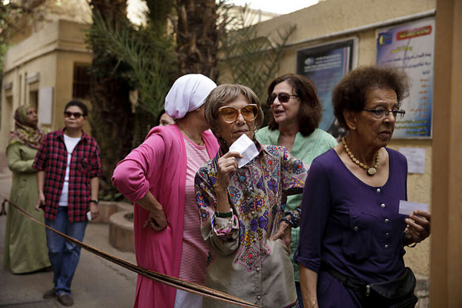 Egyptian women wait to vote at a polling site in an election that comes nearly a year after the military's ouster of the nation's first freely elected president, the Islamist Mohammed Morsi in Cairo, Egypt, Monday, May 26, 2014. The man who removed Morsi, retired military chief Field Marshal Abdel-Fattah el-Sissi, is practically assured of a victory in the vote. (AP Photo/Maya Alleruzzo)
