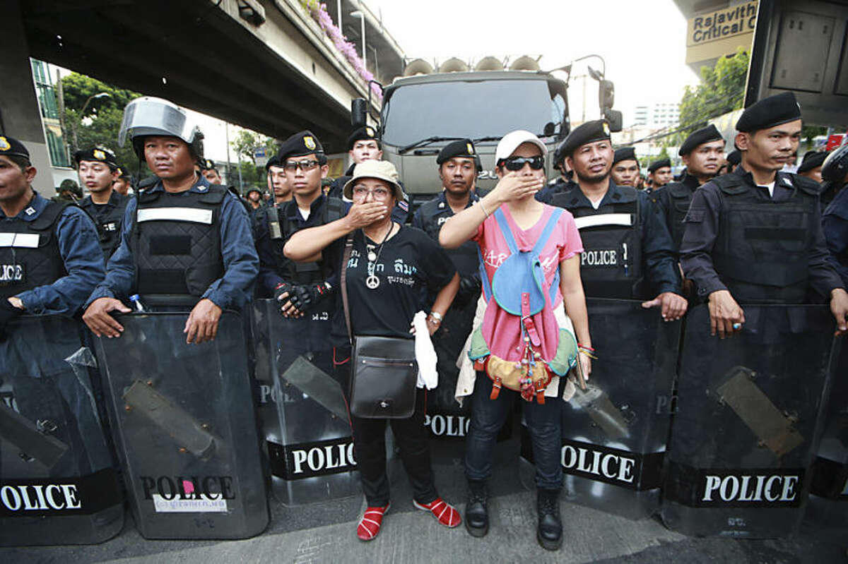 Two protesters, center, gesture in front of line of Thai riot police officers during an anti-coup demonstration at the Victory Monument in Bangkok, Thailand Monday, May 26, 2014. Bolstered by a royal endorsement Monday to run the country after last week's coup, Thailand's junta leader warned citizens not to cause trouble, not to criticize, not to protest, or else face a return to the