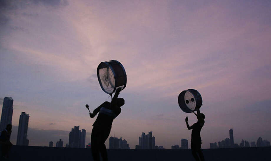Two men play drums while practicing for a choreography for a parade, in Panama City, Monday, May 26, 2014. (AP Photo/Arnulfo Franco)