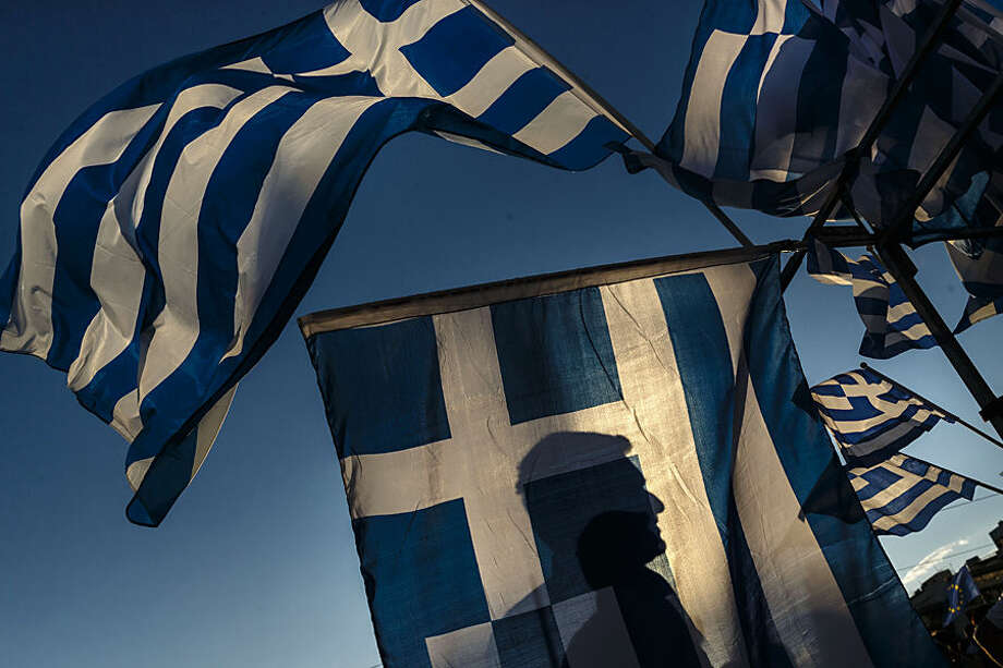 A pro-Euro demonstrator is silhouetted behind a Greek flag during a rally outside the Greek Parliament in Athens, Monday, June 22, 2015. Thousands of people gather to show support for the country's future in the eurozone and the European Union. (AP Photo/Daniel Ochoa de Olza)