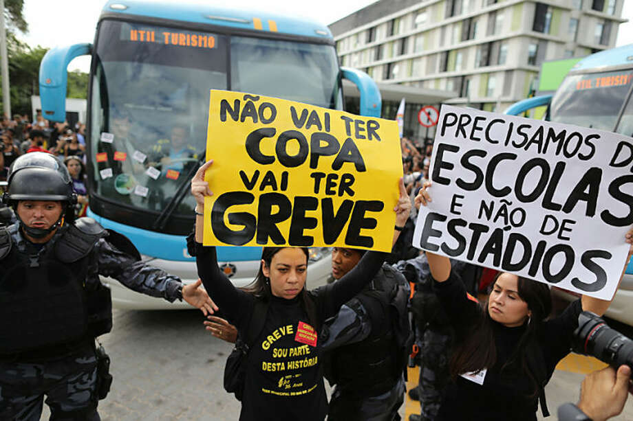 "Demonstrators hold up signs that read in Portuguese ""There won't be a Cup. There will be strikes,"" center, and ""We need schools, not stadiums"" as they walk in front of the bus carrying members of Brazil's national soccer team as it leaves a hotel for the Granja Comary training center, where the team will train and reside during the World Cup, in Rio de Janeiro, Brazil, Monday, May 26, 2014. Demonstrators are protesting the money being spent by the local government on the World Cup. (AP Photo/Leo Correa)"
