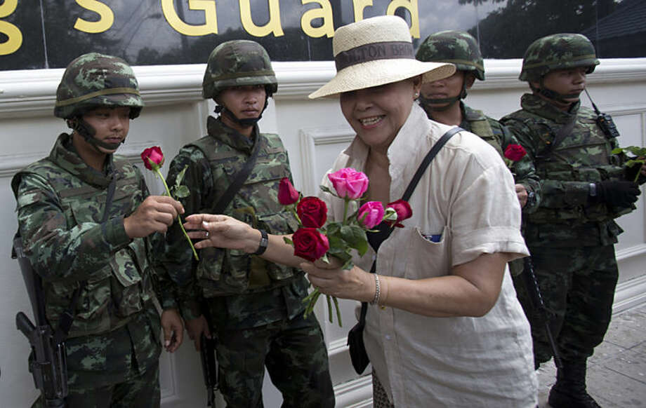 A military supporter gives a rose to a soldier in Bangkok, Thailand, Tuesday May 27, 2014. Last Thursday's military takeover, Thailand's second in eight years, deposed an elected government that had insisted for months that the nation's fragile democracy was under attack from protesters, the courts, and finally the army. (AP Photo/Sakchai Lalit)