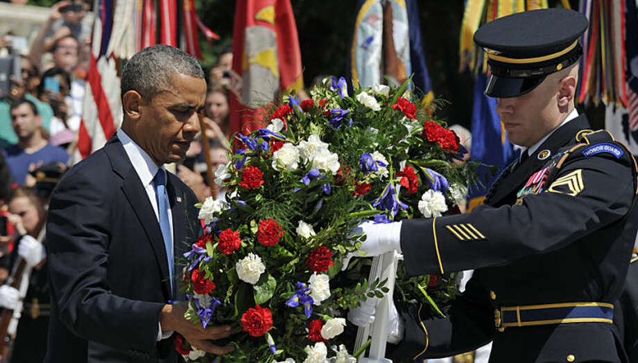 President Barack Obama lays a wreath at the Tomb of the Unknowns at Arlington National Cemetery in Arlington, Va., on Memorial Day, Monday, May 26, 2014. (AP Photo/Susan Walsh)
