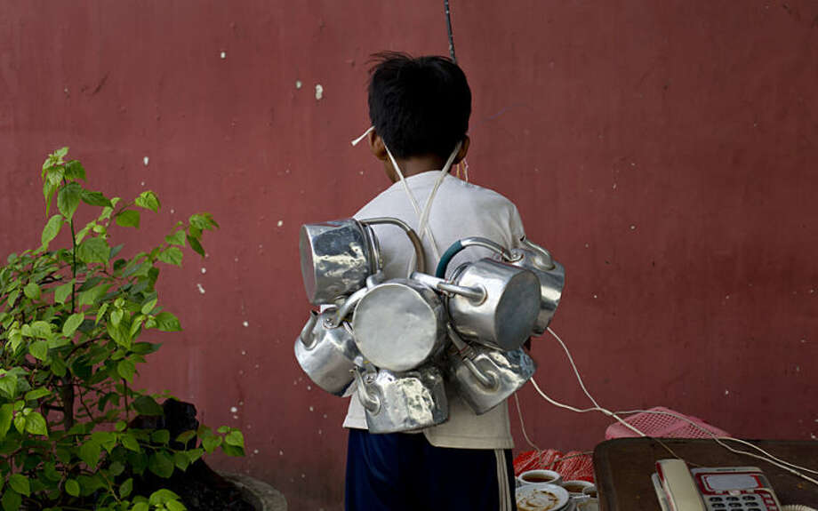 A tea delivery boy with empty tea pots attached to a rope hang on to his forehead, collects empty tea cups and tea-pots from an outdoor telephone stand in Yangon, Myanmar, Tuesday, May 27, 2014. (AP Photo/Gemunu Amarasinghe)