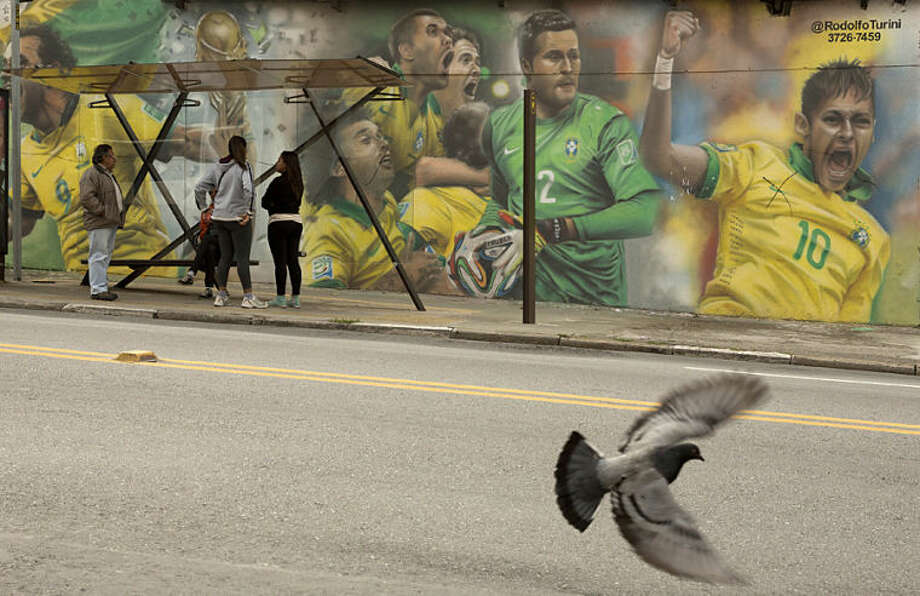 A mural of Brazilian soccer player Neymar, right, and others cover a wall by a bus stop in Sao Paulo, Brazil, Monday, May 26, 2014. The mural was painted by Brazilian street artist Rodolfo Turini ahead of the World Cup soccer tournament that starts in June. (AP Photo/Andre Penner)