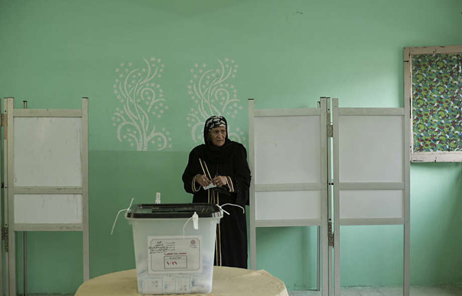 An Egyptian woman holds her ballot before casting it during the first day of a presidential election in Cairo, Egypt, Monday, May 26, 2014. This week's key vote is taking place against a backdrop of the turmoil that has roiled the country since the 2011 ouster of Hosni Mubarak and the government's crackdown against Morsi's Muslim brotherhood and its allies since last July. (AP Photo/Nariman El-Mofty)