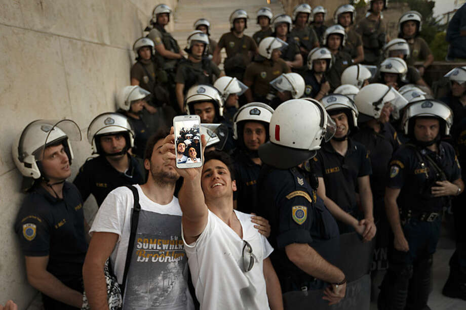 Pro-Euro demonstrators take a photograph in front of riot police outside the Greek Parliament during a rally in Athens, Monday, June 22, 2015. Thousands of people gather to show support for the country's future in the eurozone and the European Union. (AP Photo/Daniel Ochoa de Olza)