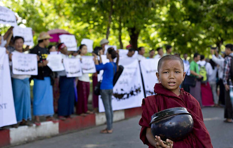 A novice Buddhist monk stands in front of a group of protesting people in Yangon, Myanmar, Tuesday, May 27, 2014. The small group of civil society activists staged a protest calling for an amendment to Myanmar's constitution that bans opposition leader Aung San Suu Kyia becoming the country's president. (AP Photo/Gemunu Amarasinghe)
