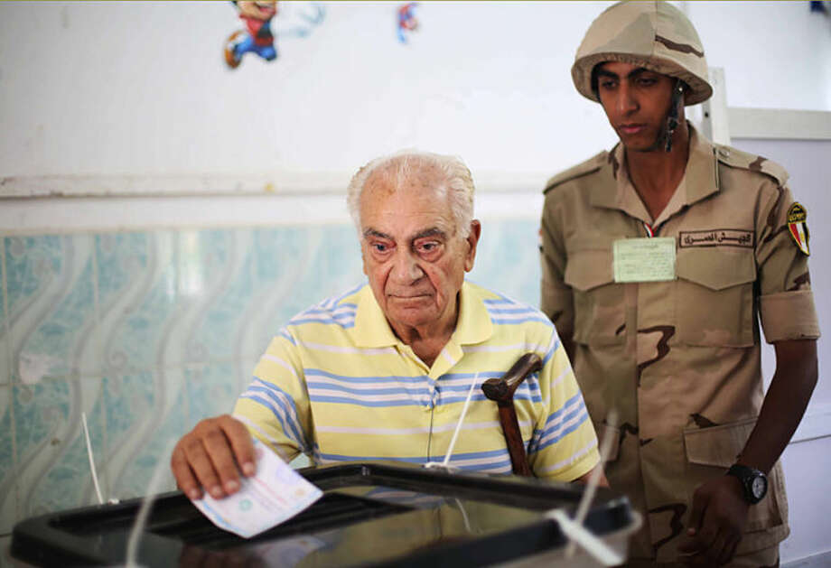 An Egyptian soldier watches a voter cast his ballot in the presidential election in Cairo, Egypt, Monday, May 26, 2014. This week's key vote is taking place against a backdrop of the turmoil that has roiled the country since the 2011 ouster of Hosni Mubarak and the government's crackdown against Morsi's Muslim brotherhood and its allies since last July. (AP Photo/Mostafa Elshemy)