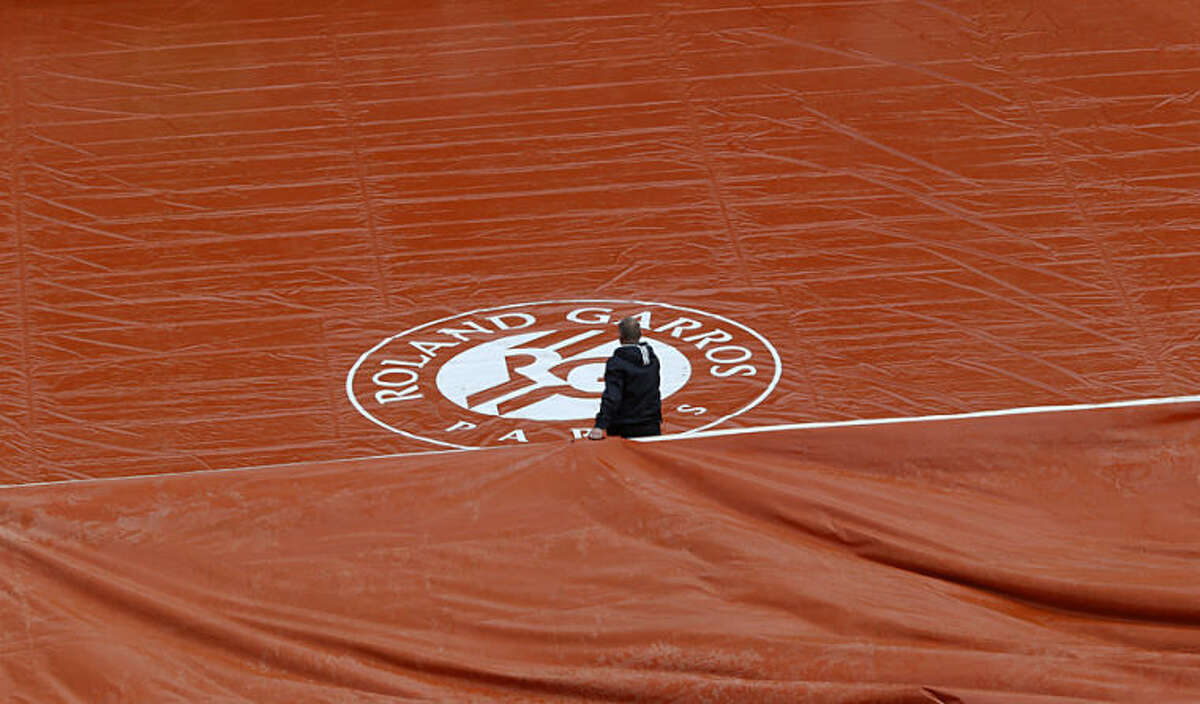 A stadium employee holds the protective canvas on center court after rain delayed the play for the first round match of the French Open tennis tournament at the Roland Garros stadium, in Paris, France, Monday, May 26, 2014. (AP Photo/Michel Euler)