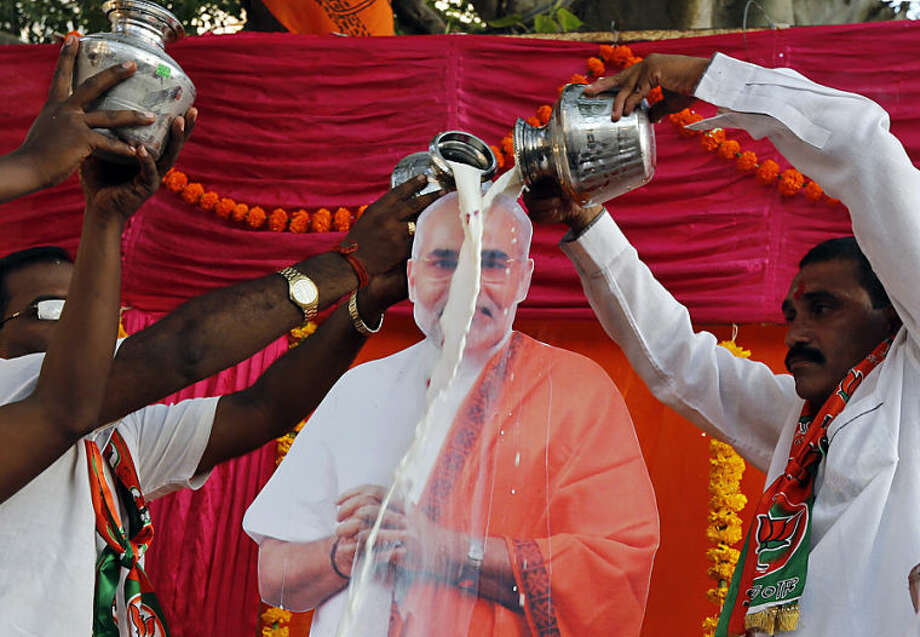 Bharatiya Janata Party supporters pour milk on a cut out photograph of India's new prime minister Narendra Modi, as they celebrate his inauguration at the Dharavi Slum in Mumbai, India, Monday, May 26, 2014. Modi took the oath of office as India's new prime minister at the sprawling presidential palace on Monday, a moment made more historic by the presence of the leader of archrival Pakistan. (AP Photo/Rajanish Kakade)