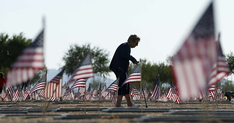 Raymonde Murphy walks past the flag-adorned graves after visiting the grave of her husband, William Murphy, a World War II veteran, at the National Memorial Cemetery of Arizona on Memorial Day, Monday, May 26, 2014, in Phoenix. (AP Photo/Ross D. Franklin)