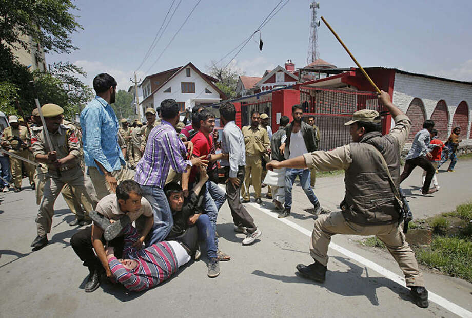 An Indian policeman approaches to beat Kashmiri government employees during a protest in Srinagar, India, Monday, May 26, 2014. Police used force to stop government employees during a protest called by the worker's union demanding regularization of contractual jobs and a hike in salary. (AP Photo/Mukhtar Khan)