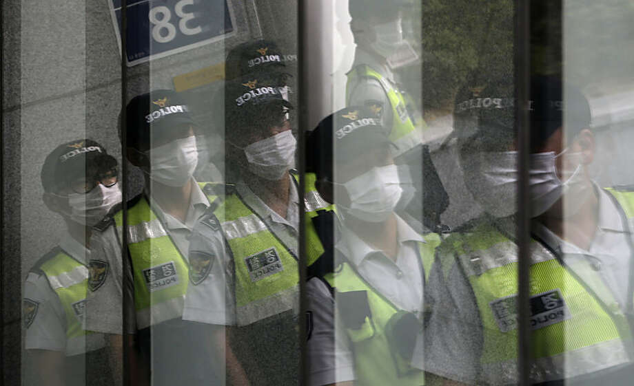 Police officers wearing masks as a precaution against Middle East Respiratory Syndrome (MERS) are reflected on windows in Seoul, South Korea, Tuesday, June 23, 2015. South Korea's MERS outbreak originated from a 68-year-old man who had traveled to the Middle East, where the illness has been centered, before being diagnosed as the country's first MERS patient last month. (AP Photo/Lee Jin-man)