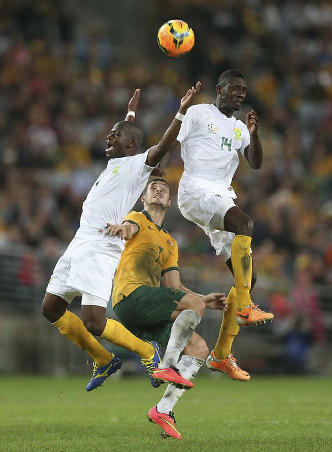 South Africa's Alpheus Hlompho Kekana, left, and team mate Erick Mathoho try to block out Australia's Matthew Leckie as they head the ball during their Soccer friendly match in Sydney, Australia, Monday, May 26, 2014.(AP Photo/Rob Griffith)