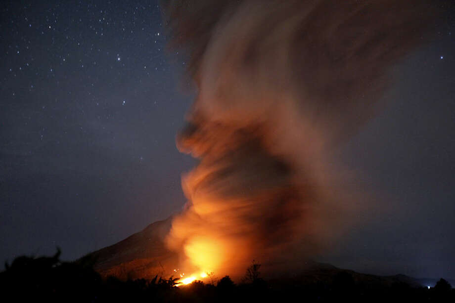In this late Monday, June 22, 2015 photo, Mount Sinabung spews pyroclastic flows as seen from Tiga Kicat, North Sumatra, Indonesia. The volcano has been at the highest alert level since June 2. (AP Photo/Binsar Bakkara)
