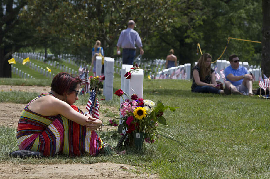 Natasha Marshall, 22, of Frederick, Md., visits the grave of her friend and high school sweetheart Army Specialist Tyler Hammett, 21, on Memorial Day at Arlington National Cemetery in Arlington, Va., Monday, May 26, 2014. Hammett died while stationed in Alabama in December of 2014. (AP Photo/Jacquelyn Martin)