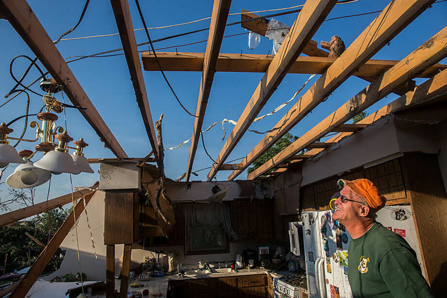 Al Burch examines damage to his kitchen on Tuesday, June 23, 2015, after a severe storm passed through Coal City, Ill. Monday night. Coal City Mayor Terry Halliday said a suspected tornado swept into town, first striking the high school before moving to the southeast over homes and damaging a fire station. (Zbigniew Bzdak/Chicago Tribune via AP)