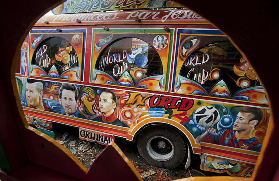 In this May 21, 2014 photo, a painting of soccer stars decorate a tap-tap passenger bus at a garage where buses are built in Port-au-Prince, Haiti. From left to right are Portugal's Cristiano Ronaldo, Argentina's Lionel Messi, Sweden's Zlatan Ibrahimovic, and Brazil's Neymar. The brightly painted Haitian minibuses known as tap-taps are getting a bit more colorful in the lead up to the World Cup. (AP Photo/Dieu Nalio Chery)