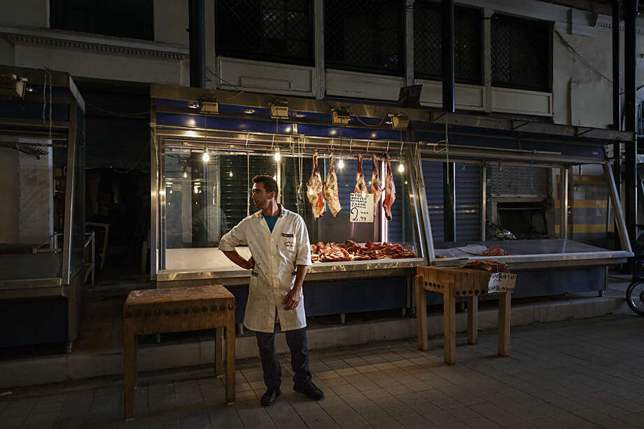 A butcher wait for clients in a market in Athens, Tuesday, June 23, 2015 . Greece this week offered a series of measures, including multiple tax increases, to persuade its creditors to release bailout funds and keep the country from defaulting on its debts as soon as next week. (AP Photo/Daniel Ochoa de Olza)