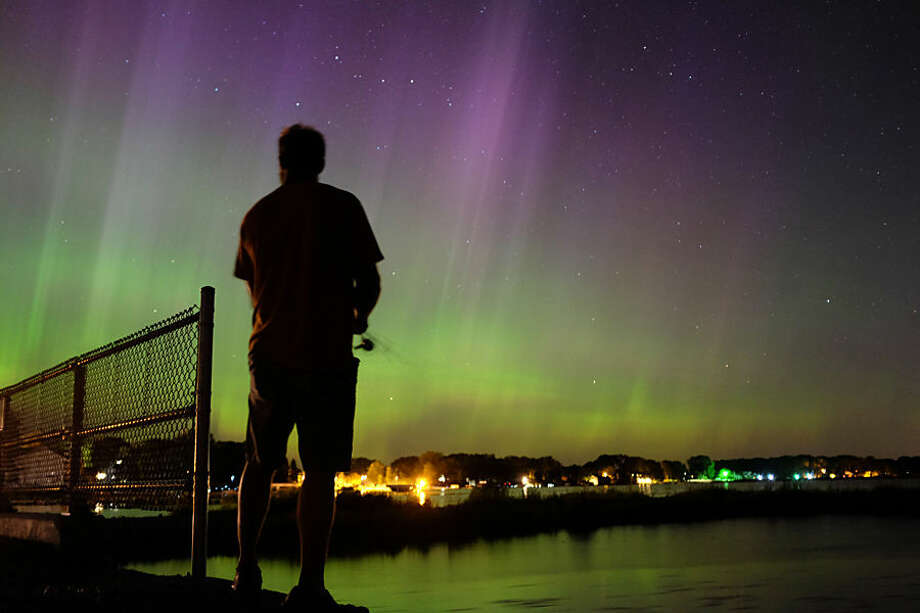 Wade Kitner looks at the northern lights as he fishes in Ventura, Iowa, on Tuesday, June 23, 2015. Federal forecasters said the Northern Lights may be able to be seen Tuesday night as far south as Iowa or Pennsylvania because of a severe solar storm that hit the Earth on Monday and pushes auroras to places where more people can possibly see them. (Arian Schuessler, The Globe Gazette via AP)