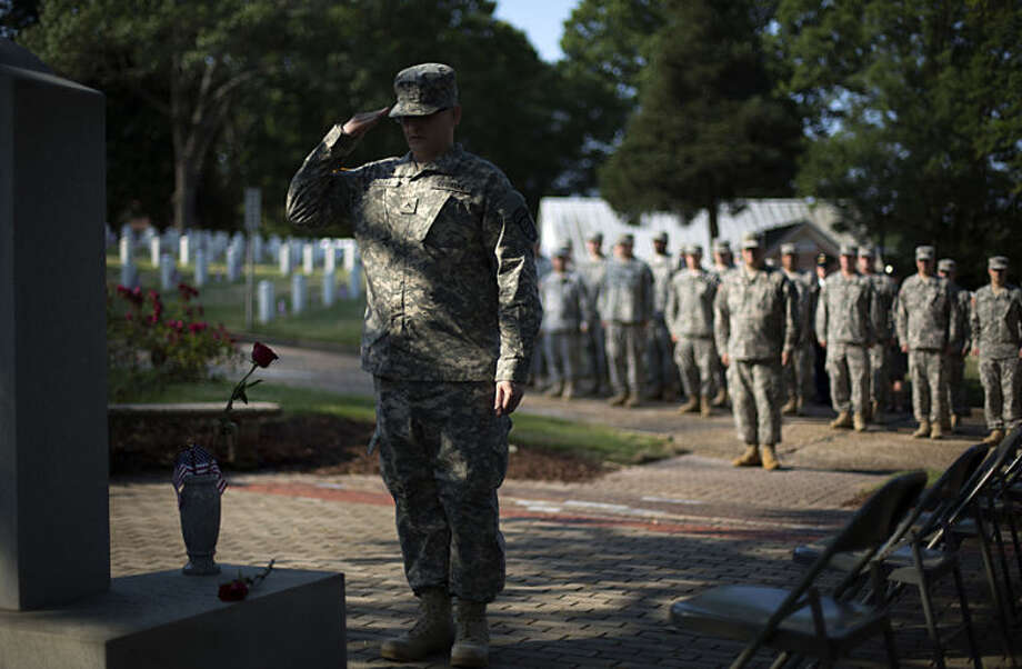 Pvt. John Schena, with the 2nd Battalion 1st Brigade of the Georgia State Defense Force, salutes after placing a rose at a Pearl Harbor Memorial at Marietta National Cemetery on Memorial Day, Monday, May 26, 2014, in Marietta, Ga. (AP Photo/David Goldman)