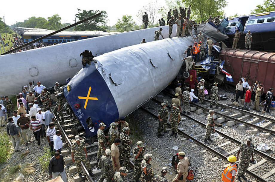 Indian officials and rescuers stand near the wreckage after the Gorakhpur Express passenger train slammed into a parked freight train Chureb, near Basti, Uttar Pradesh state, India, Monday, May 26, 2014. According to officials at least 40 were killed. (AP Photo)