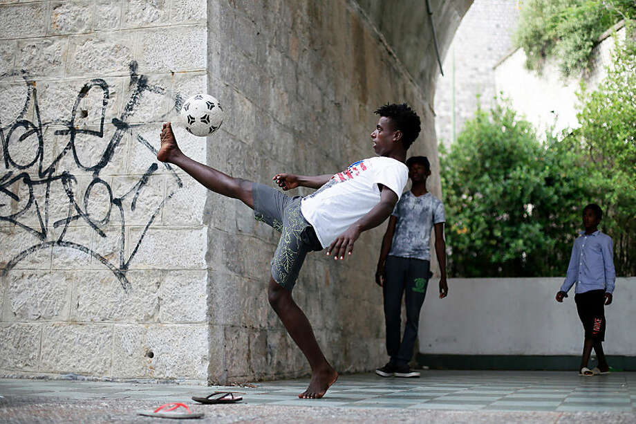 Abraham Hilan 17, from Eritrea, plays soccer at the Franco-Italian border in Ventimiglia, Italy, Sunday, June 21, 2015. European Union nations failed to bridge differences Tuesday, June 16 over an emergency plan to share the burden of the thousands of refugees crossing the Mediterranean Sea, while on the French-Italian border, police in riot gear forcibly removed dozens of migrants. (AP Photo/Thibault Camus)