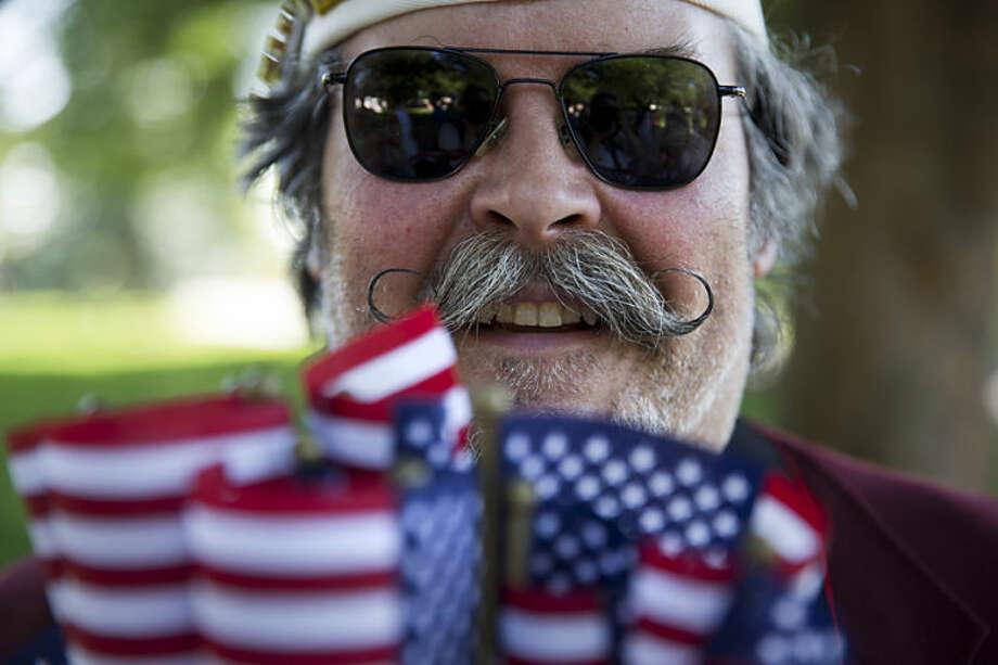 Navy veteran Mike Bukowski, of Virginia Beach, Va., hands out small U.S. flags at Arlington National Cemetery in Arlington, Va., for Memorial Day Monday, May 26, 2014. (AP Photo/Jacquelyn Martin)