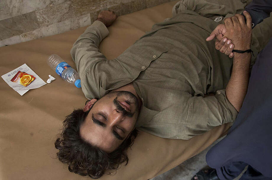 A Pakistani patient suffering from heatstroke waits for medical help at a local hospital in Karachi, Pakistan, Tuesday, June 23, 2015. A scorching heat wave across southern Pakistan's city of Karachi has killed more than 400 people, authorities said Tuesday, as morgues overflowed with the dead and overwhelmed hospitals struggled to aid those clinging to life. (AP Photo/Shakil Adil)