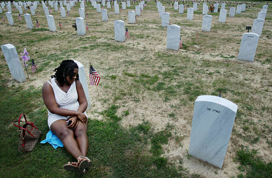LaToya White leans on the head stone of her step-father Marine Lance Cpl. Willie Scott Jr., who served in Korea, on Memorial Day at West Tennessee Veterans Cemetery in Memphis, Tenn. Monday, May 26, 2014. (AP Photo/The Commercial Appeal, Mike Brown)