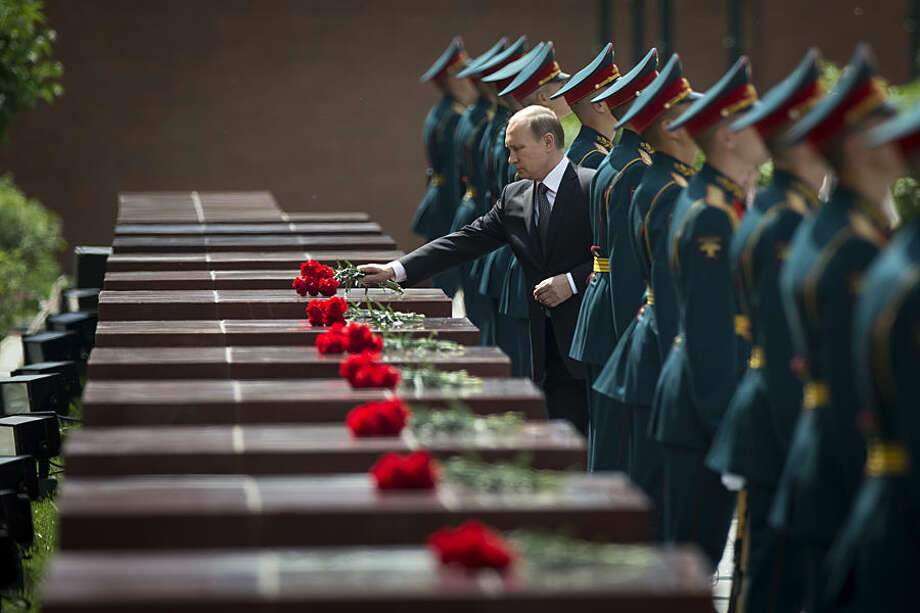 Russian President Vladimir Putin, center, takes part in a wreath laying ceremony at the Tomb of the Unknown Soldier outside Moscow's Kremlin Wall, in Moscow, Russia, Monday, June 22, 2015, to mark the 74th anniversary of the Nazi invasion of the Soviet Union. (AP Photo/Alexander Zemlianichenko)