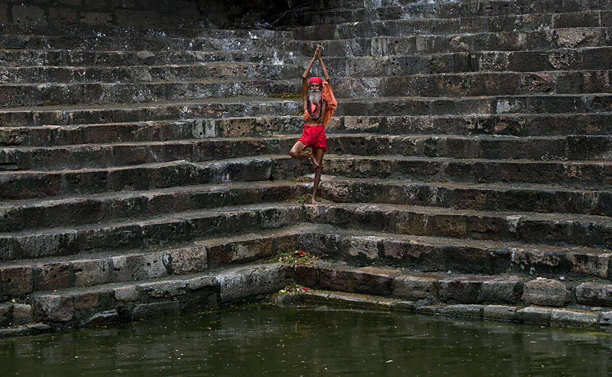 A Sadhu or Hindu holy man performs yoga on the steps of Saubhagya Kund, a holy pond, at the Kamakhya temple in Gauhati, India, Tuesday, June 23, 2015. Hundreds of Sadhus, or Hindu holy men, have arrived for the five-day festival to perform rituals at the temple during the annual Ambubasi festival that began Monday. (AP Photo/Anupam Nath)