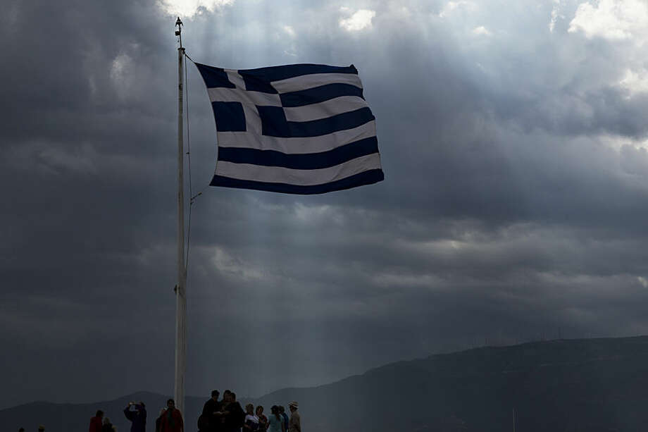 A Greek flag waves as the sun's rays shine through clouds at the ancient Acropolis hill, in Athens, Monday June 22, 2015. A top European Union official said that debt talks between Greece and its international creditors have made some progress but that a deal to avoid potential bankruptcy remains elusive. (AP Photo/Petros Giannakouris)
