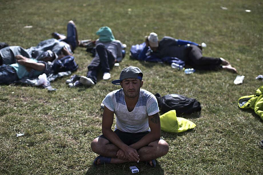 A Syrian Kurdish migrant tries to rest at a park in Presevo, close to the Serbian border with Macedonia, 300 kilometers southeast of Belgrade, Serbia, Monday, June 22, 2015. As Serbia struggles to cope with the rush of migrants crossing its territory, officials said Monday that the Hungarian police will help patrol the Serbia-Macedonia border to try to stem the flow of migrants and refugees attempting to reach the EU. (AP Photo/Marko Drobnjakovic)