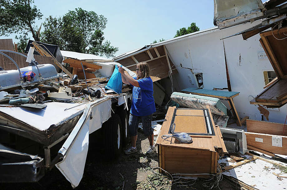 Julie Hersom goes through what's left of her camper after severe weather moved through the area, damaging trees, homes and other structures Monday, June 22, 2015, in Garretson, S.D. Thunderstorms caused damage throughout eastern South Dakota, leaving thousands of people without power and zeroing in on the town of Garretson, where damage was particularly extensive. (Joe Ahlquist/The Argus Leader via AP) NO SALES