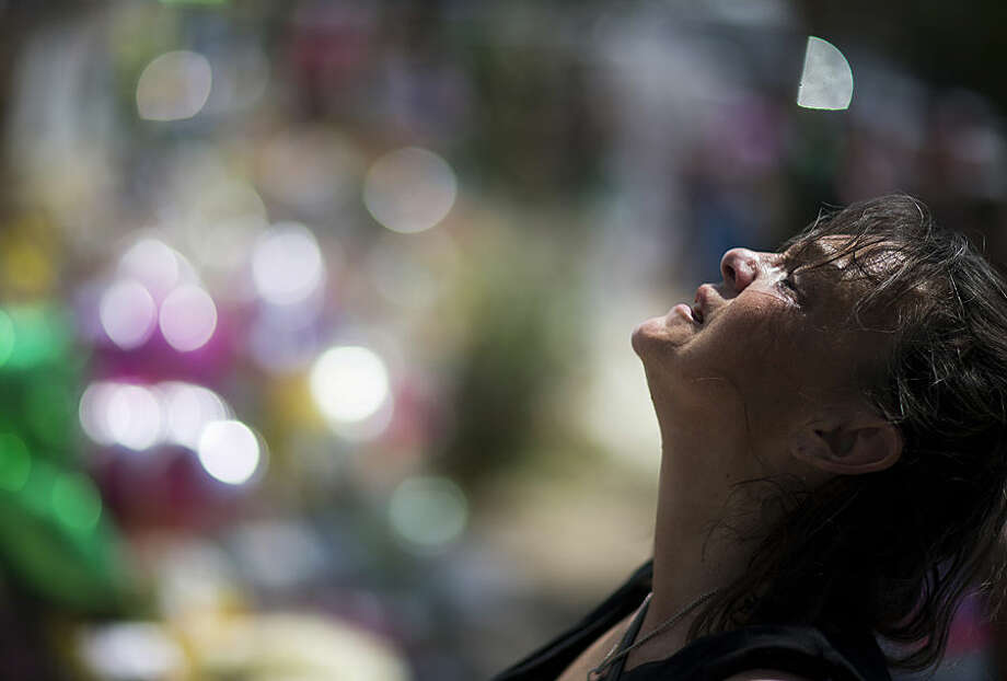 Auburn Sandstrom cries while praying at a sidewalk memorial in memory of the shooting victims in front of Emanuel AME Church, Monday, June 22, 2015, in Charleston, S.C. A week of funerals lie ahead for victims of the Charleston church massacre that killed nine people. (AP Photo/David Goldman)
