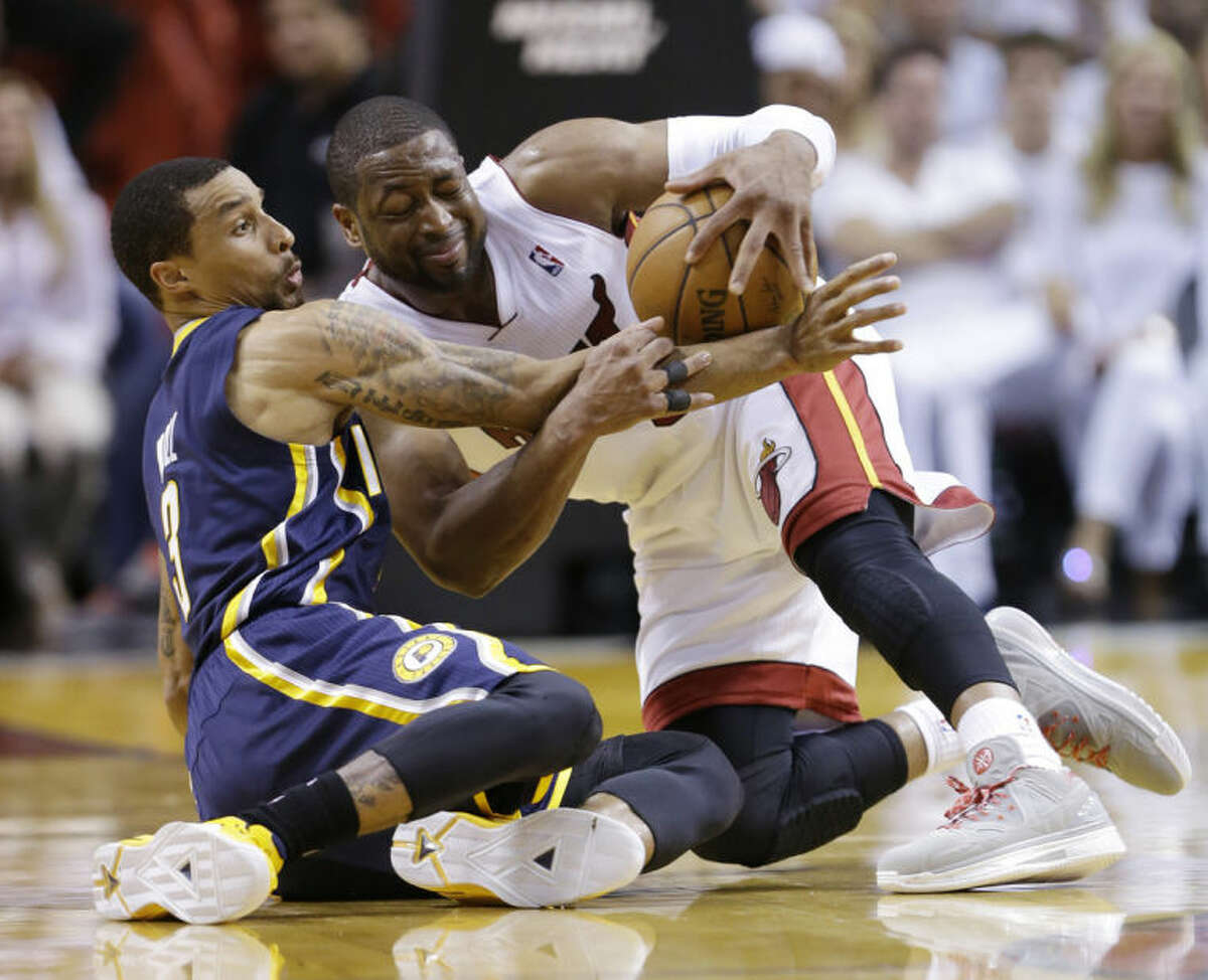 Indiana Pacers guard George Hill, left, and Miami Heat guard Dwyane Wade, fight over a loose ball during the first half of Game 4 in the NBA basketball Eastern Conference finals playoff series, Monday, May 26, 2014, in Miami. (AP Photo/Wilfredo Lee)