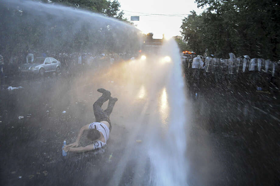 Armenian police use water canons to disperse protesters demonstrating an increase in electricity prices in the Armenian capital of Yerevan, Tuesday, June 23, 2015. Police in the Armenian capital have dispersed several hundred demonstrators who blocked a central avenue as part of their protest. About 5,000 demonstrators gathered Tuesday morning in downtown, but were stopped by phalanxes of riot police backed by water cannons. (Narek Aleksanyan/PAN Photo via AP)
