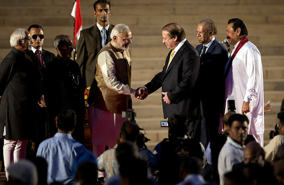 India's new prime minister Narendra Modi, center left, shakes hands with his Pakistani counterpart Nawaz Sharif, as Sri Lankan President Mahinda Rajapaksa, right, and Mauritius Prime Minister Navinchandra Ramgoolam, second right watch during Modi's inauguration in New Delhi, India, Monday, May 26, 2014. Modi took the oath of office as India's new prime minister at the sprawling presidential palace on Monday, a moment made more historic by the presence of the leader of archrival Pakistan. Indian President Pranab Mukherjee, third left and Indian Vice President Hamid Ansari, left, are also seen. (AP Photo /Manish Swarup)