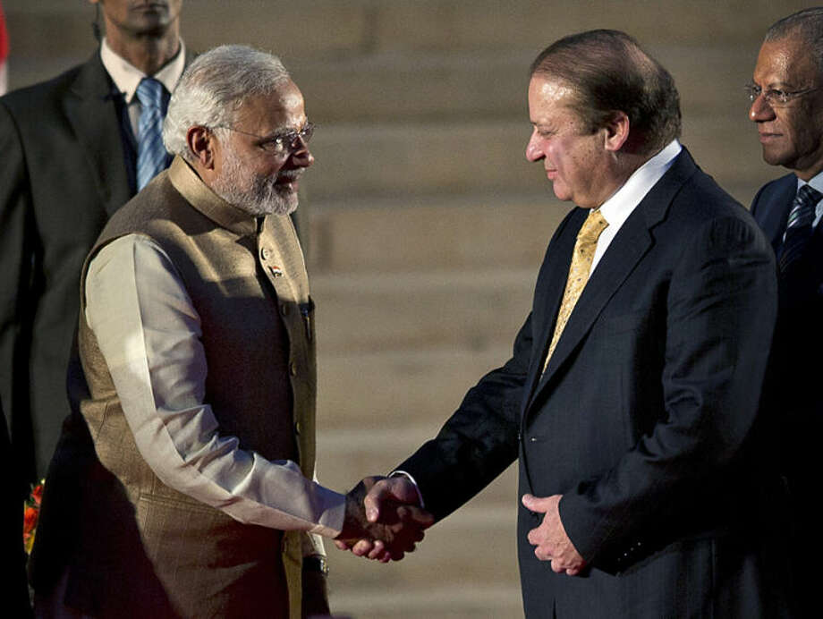 India's new prime minister Narendra Modi, left, shakes hands with his Pakistani counterpart Nawaz Sharif, as Mauritius Prime Minister Navinchandra Ramgoolam, right, watches during Modi's inauguration in New Delhi, India, Monday, May 26, 2014. Modi took the oath of office as India's new prime minister at the sprawling presidential palace on Monday, a moment made more historic by the presence of the leader of archival Pakistan. (AP Photo/Manish Swarup)
