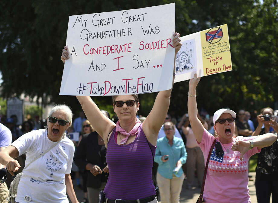 Protesters hold signs as they chant during a rally to take down the Confederate flag at the South Carolina Statehouse, Tuesday, June 23, 2015, in Columbia, S.C. The shooting deaths of nine people at a black church in Charleston, S.C, have reignited calls for the Confederate flag flying on the grounds of the Statehouse in Columbia to come down. Rallies are being held, and politicians have joined the chorus of voices calling for its removal — an opinion that has carried political risks in the state in the past. (AP Photo/Rainier Ehrhardt)