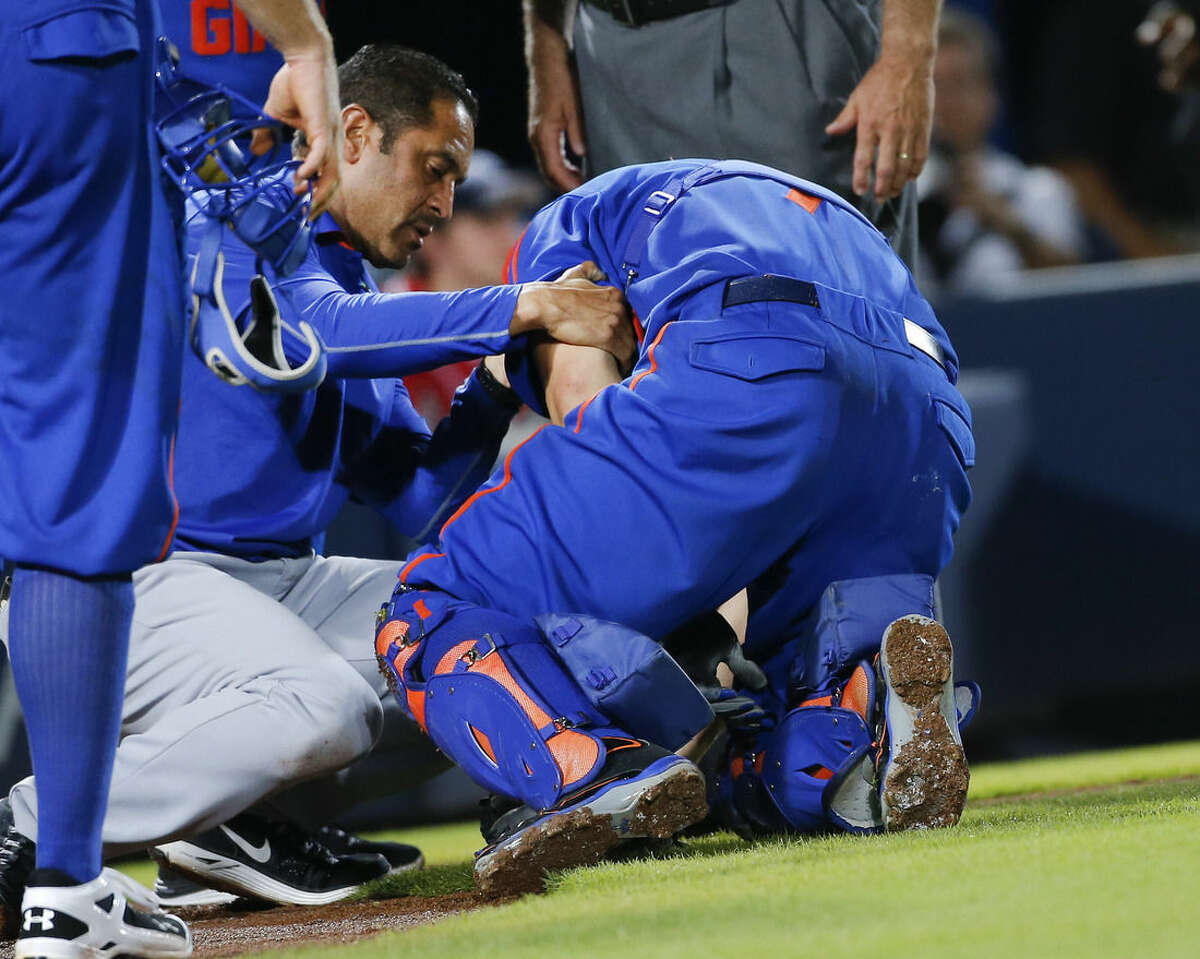 A member of New York Mets training staff attends to catcher Travis d'Arnaud (7) after he was injured in the sixth inning of a baseball game against the Atlanta Braves Saturday, June 20, 2015, in Atlanta. d'Arnuad left the game. (AP Photo/John Bazemore)