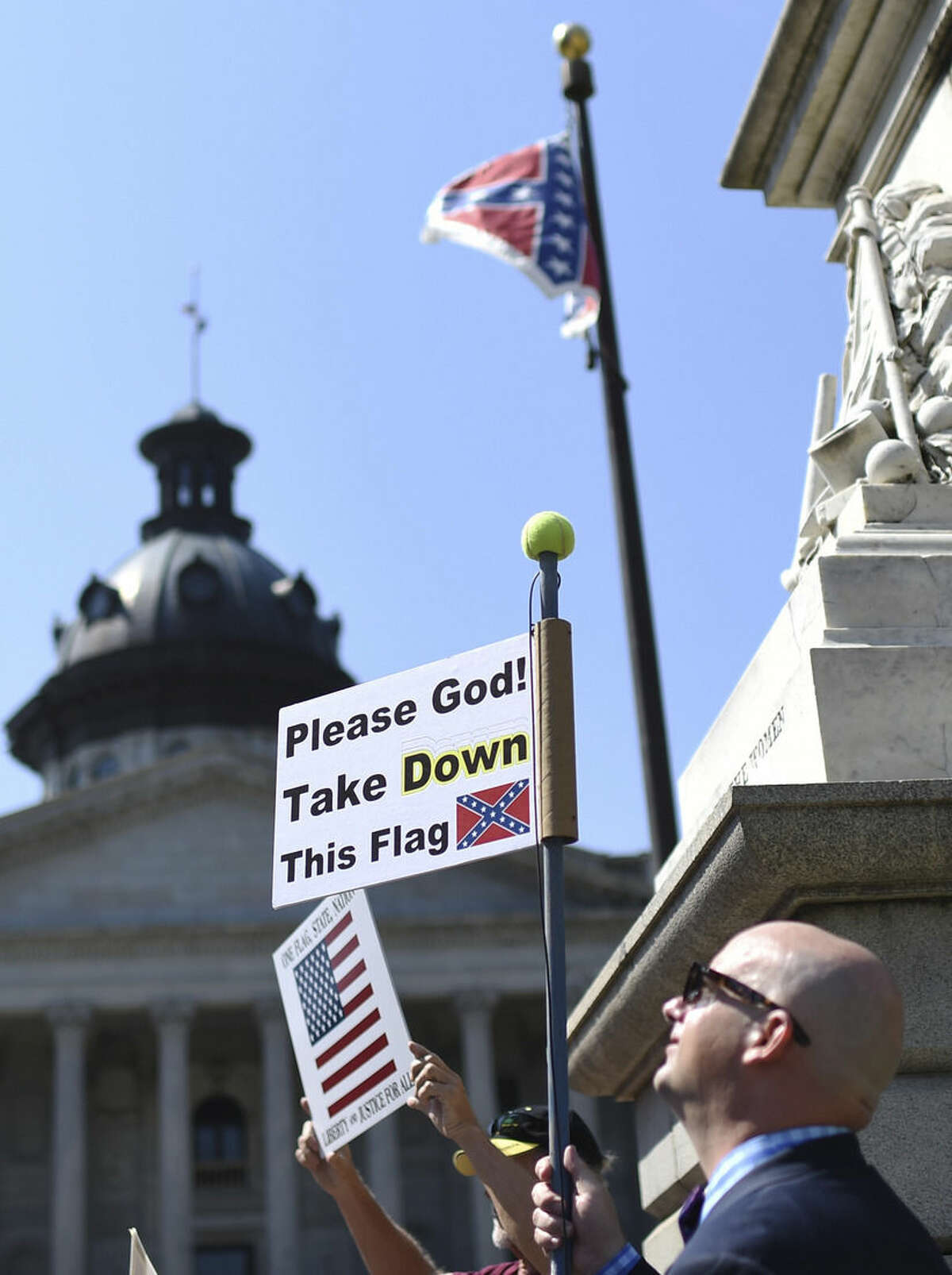 Christian Mergner, of Columbia, S.C., holds a sign during a rally to take down the Confederate flag at the South Carolina Statehouse, Tuesday, June 23, 2015, in Columbia, S.C. The shooting deaths of nine people at a black church in Charleston, S.C, have reignited calls for the Confederate flag flying on the grounds of the Statehouse in Columbia to come down. Rallies are being held, and politicians have joined the chorus of voices calling for its removal - an opinion that has carried political risks in the state in the past. (AP Photo/Rainier Ehrhardt)