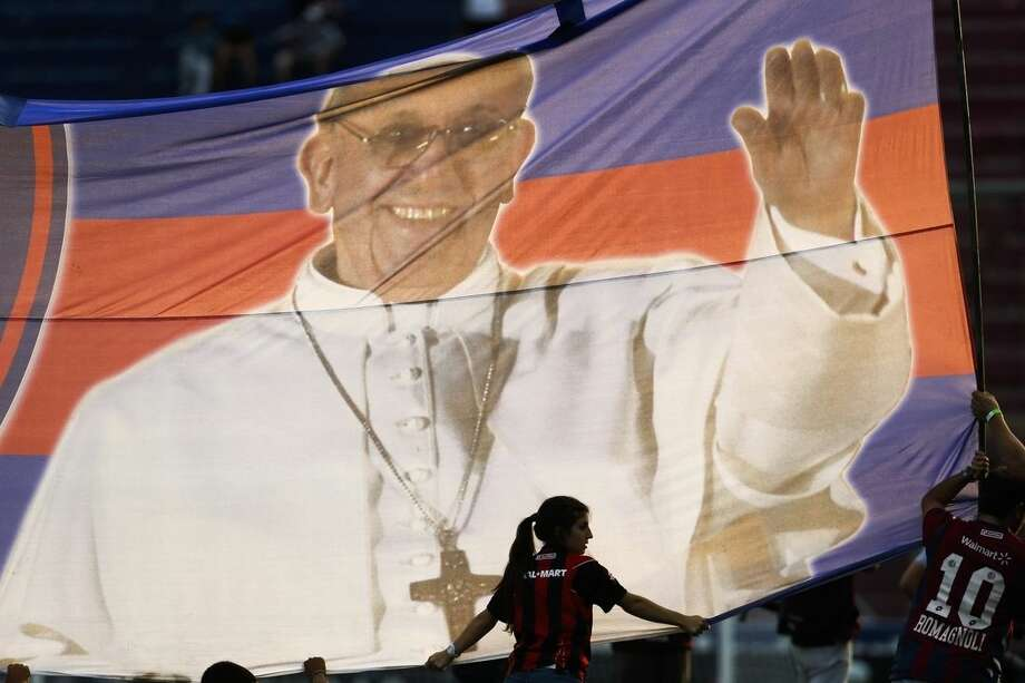 FILE - In this March 31, 2013, file photo, fans hold a banner with a photo of Pope Francis and the colors of the San Lorenzo de Almagro soccer club before a Argentine Primera División soccer match between Newell's Old Boys and San Lorenzo de Almagro in Buenos Aires, Argentina. Pope Francis clearly embraces his Argentine identity. He's a self-proclaimed fan of the country's San Lorenzo, as well as its traditional tango dancing and milonga music. (AP Photo/Victor R. Caivano, File)
