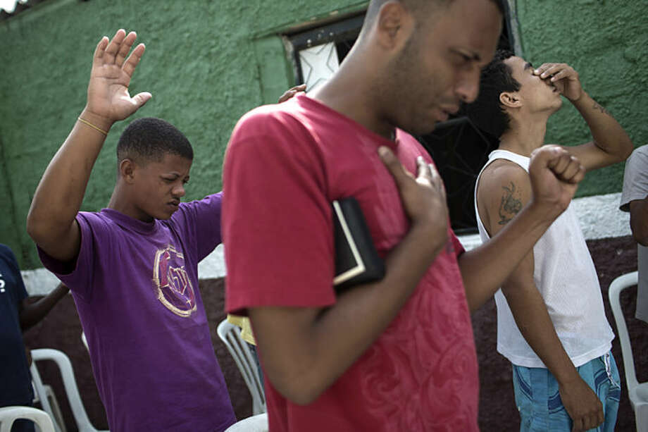 "In this May 9, 2014 photo, former drug users react during a morning prayer at the God's Love rehabilitation center in Rio de Janeiro, Brazil. Pastor Celio Ricardo offers them a roof in a makeshift shelter in a nearby neighborhood, a simple structure next to his humble Love of God evangelical church. On a recent day, 25 young men gathered in a circle outside the shelter, lifting their hands to the sky and shouting, ""Glory to God! Glory to God!"" (AP Photo/Felipe Dana)"