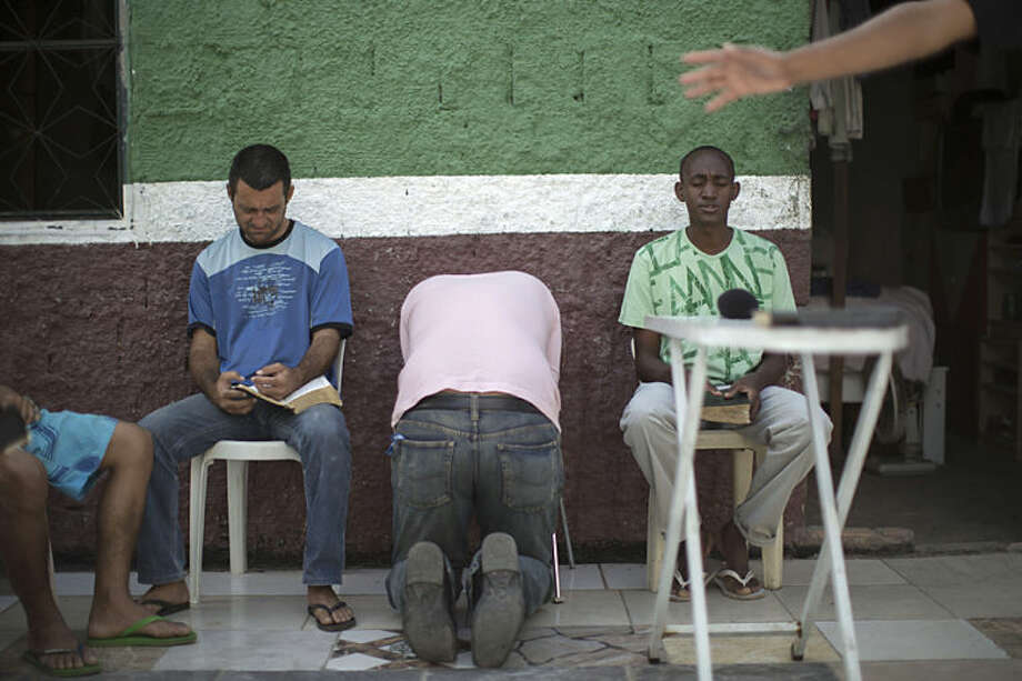 In this May 9, 2014 photo, former drug users pray at the God's Love rehabilitation center in Rio de Janeiro, Brazil. Pastor Celio Ricardo, who leads the team of street preachers, has had hit-and-miss success in persuading some users to at least try quitting. He offers them a roof in a makeshift shelter in a nearby neighborhood, a simple structure next to his humble Love of God evangelical church. (AP Photo/Felipe Dana)